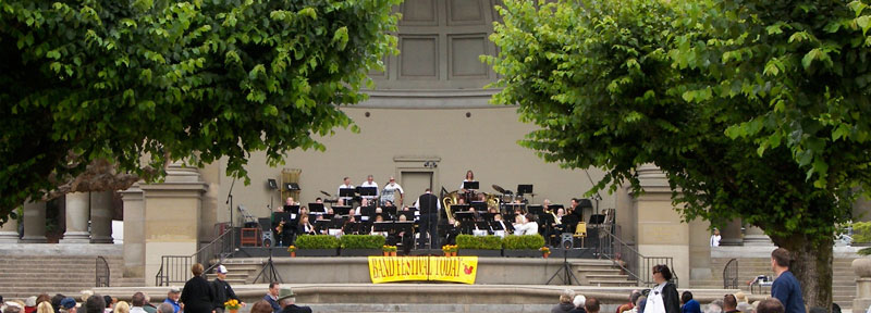"Band playing Golden Gate Park Band Shell with sign reading ""Band Festival Today""."